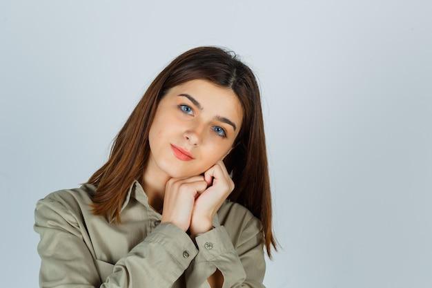 シャツの握りしめられた手に頬をもたれ、賢明に見える若い女性。正面図。