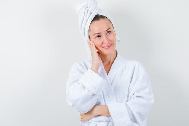 白いバスローブ、タオルで手に頬を傾けて、穏やかな正面図を探している若い女性。