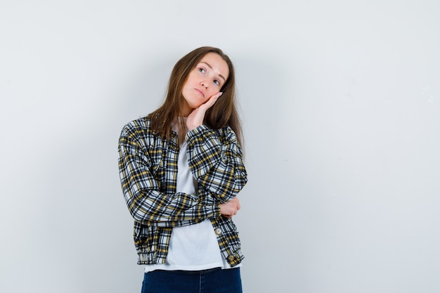 Tシャツ、ジャケットで手のひらに頬をもたれ、思慮深く見える若い女性。正面図。