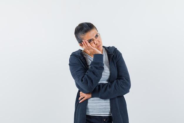 Молодая дама, опираясь щекой на ладонь в футболке