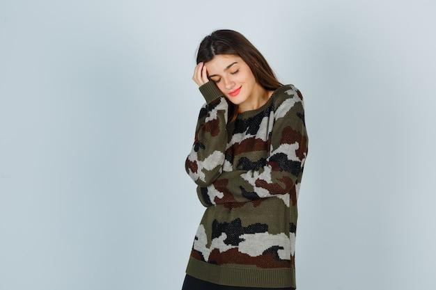 Giovane signora che si appoggia sulla guancia sul palmo in maglione, gonna e sembra pacifica
