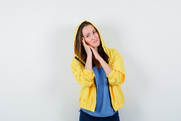 Giovane donna che si appoggia guancia sul palmo in maglietta, giacca e sembra triste. vista frontale.