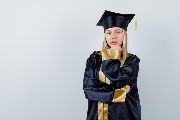 Giovane signora che si appoggia il mento sul pugno in abito accademico e sembra sicura.