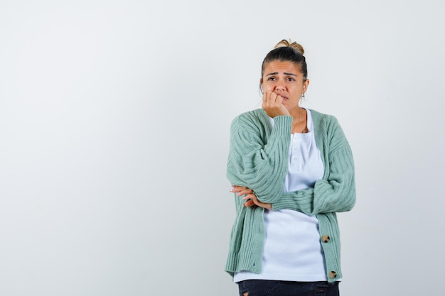 Giovane donna che si appoggia il mento in mano in maglietta, giacca e sembra pensierosa