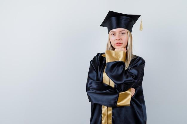 アカデミックドレスで拳に顎をもたれ、自信を持って見える若い女性。