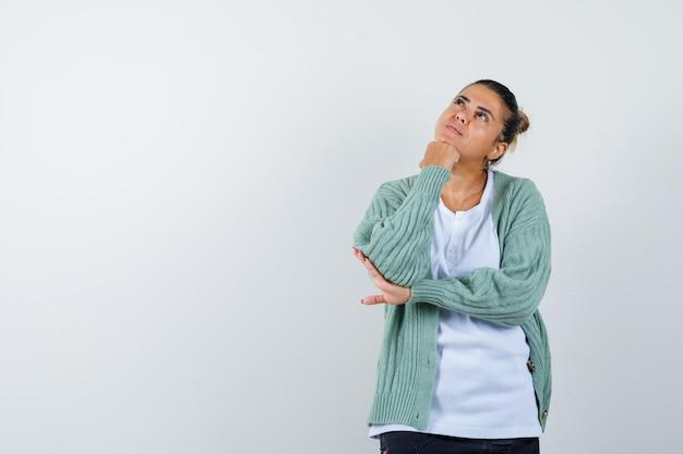 Tシャツ、ジャケット、思慮深く見える拳に顎をもたれている若い女性