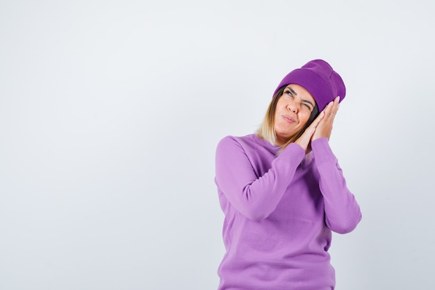 Young lady leaning on hands as pillow in purple sweater, beanie and looking joyful. front view.