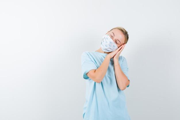 Молодая дама опирается на руки как подушку в футболке, маске и выглядит мирно