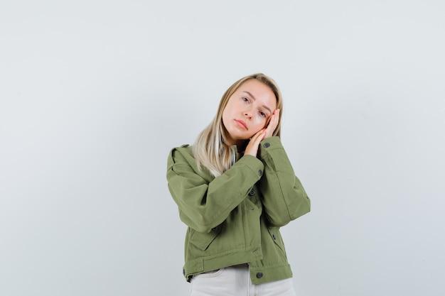ジャケット、ズボンの枕として手のひらに寄りかかって物思いにふける若い女性。正面図。