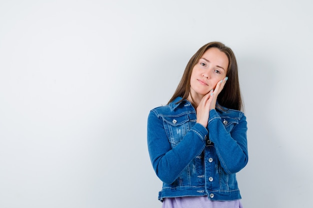 Tシャツ、ジャケットの枕として手のひらに寄りかかって、賢明に見える若い女性。正面図。