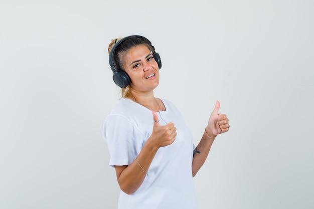 Девушка слушает музыку, показывая двойные пальцы вверх в футболке вид спереди.