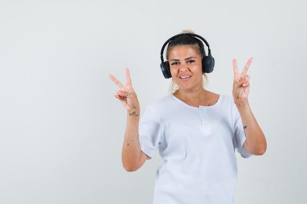 Девушка слушает музыку, показывая v-знак в футболке, вид спереди.