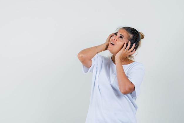 Молодая дама слушает музыку в наушниках в футболке