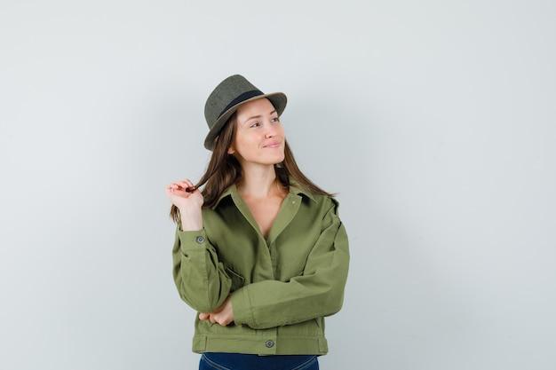 Молодая дама смотрит в сторону в куртке, штанах и шляпе и выглядит мирно