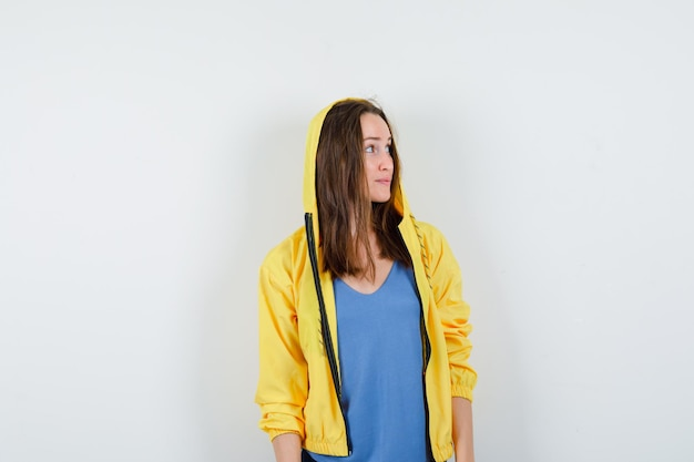 Tシャツ、ジャケットで脇を見て、希望に満ちた若い女性