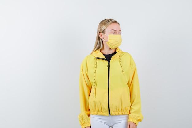 Giovane donna che osserva da parte in giacca, pantaloni, maschera e sguardo pensieroso, vista frontale.