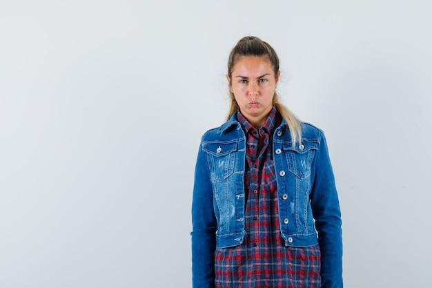 Молодая дама смотрит в камеру в рубашке, куртке и выглядит упрямым, вид спереди.