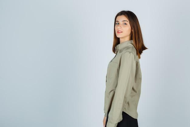 셔츠, 치마를 입은 카메라를 보고 쾌활한 젊은 여성.