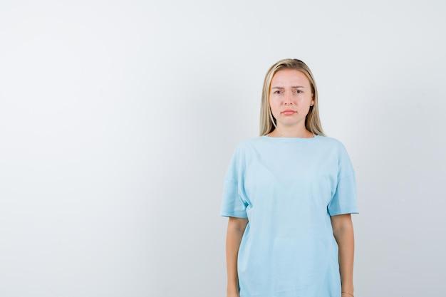 젊은 아가씨 티셔츠에 카메라를보고 고립 된 불쾌감을 찾고