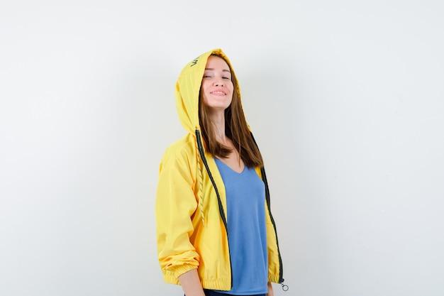 Tシャツ、ジャケットでカメラを見て、誇らしげに見える若い女性。