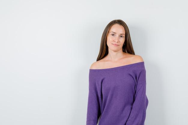 Молодая дама смотрит в камеру в фиолетовой рубашке и выглядит мило, вид спереди.