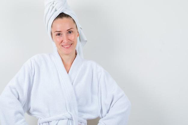 白いバスローブ、タオルでカメラを見て、陽気に見える若い女性、正面図。