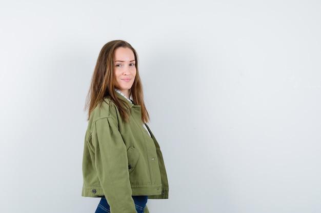 シャツ、ジャケット、魅力的に見える彼女の肩越しにカメラを見ている若い女性。