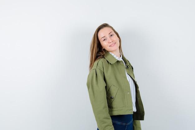 シャツ、ジャケットでポーズをとって、魅惑的な正面図を見ながらカメラを見ている若い女性。