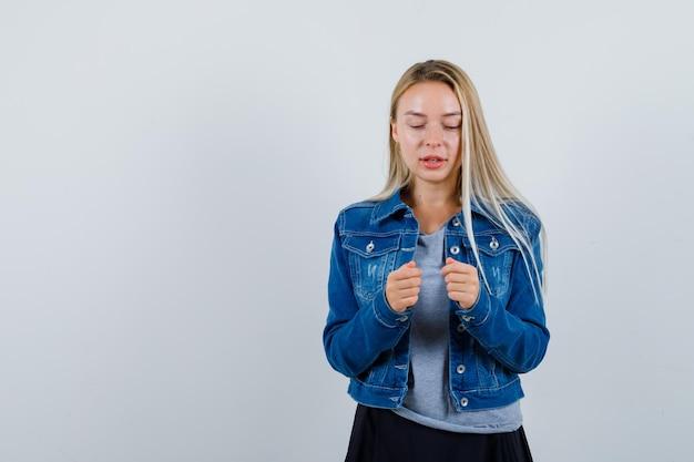 티셔츠, 데님 재킷, 스커트에 주먹을보고 사려 깊은 찾고 젊은 아가씨