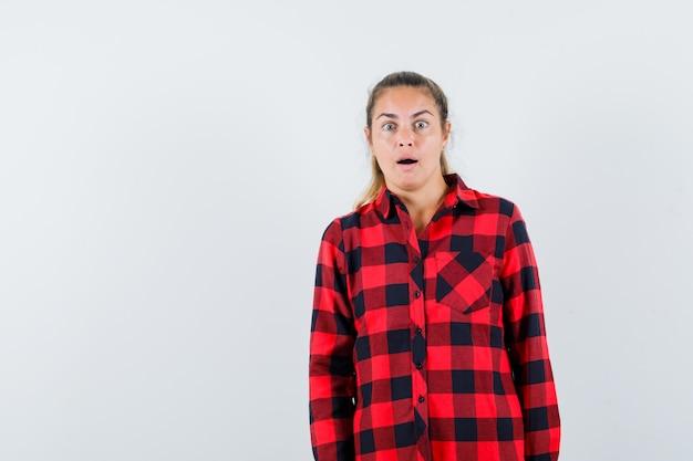 Молодая дама смотрит вперед в клетчатой рубашке и с удивлением смотрит
