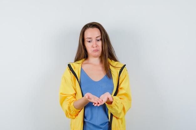 Молодая дама смотрит на свои сложенные чашкой руки в футболке и выглядит озадаченным. передний план.
