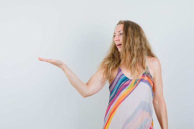 Девушка в летнем платье смотрит на раздвинутую ладонь и смотрит с надеждой