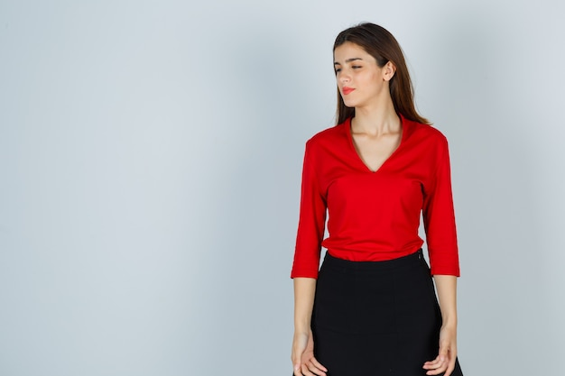 Young lady looking away in red blouse, skirt and looking pensive