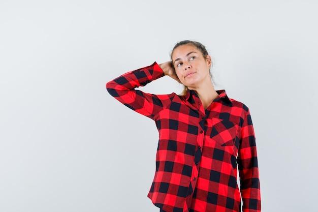 Giovane donna che guarda lontano con la mano sulla testa in camicia a quadri e sembra sognante