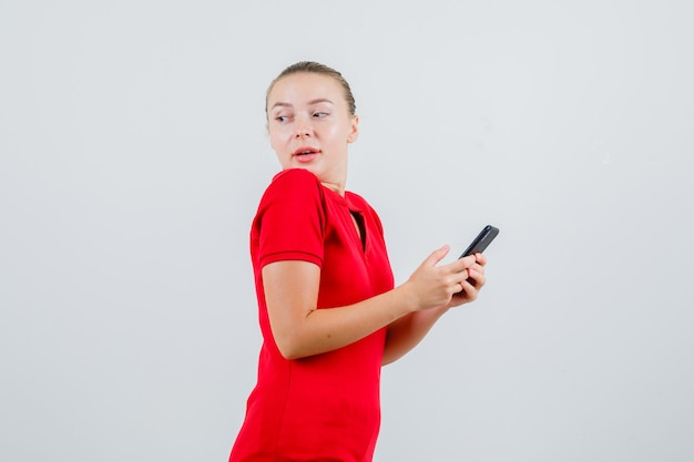 Молодая леди, оглядываясь назад, держа мобильный телефон в красной футболке и с любопытством глядя.