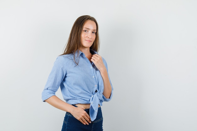 Young lady looking at camera in blue shirt, pants and looking sensible.