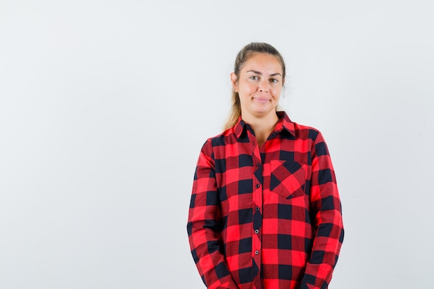 Giovane donna che guarda l'obbiettivo in camicia casual e guardando allegro, vista frontale.