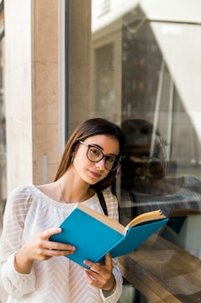 Young lady looking at camera and holding book near window