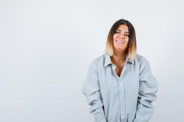 Giovane donna che guarda l'obbiettivo in camicia oversize e guardando gioiosa, vista frontale.