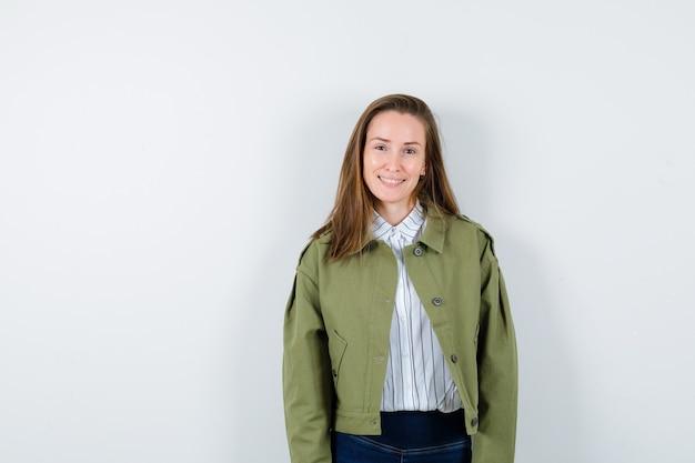 Giovane donna che guarda l'obbiettivo in camicia, giacca e guardando accattivante, vista frontale.