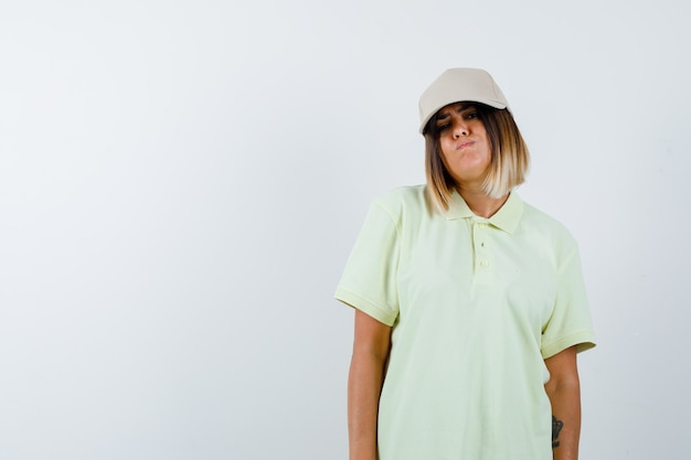 Young lady looking at camera in t-shirt, cap and looking wistful , front view.
