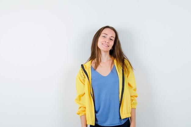 Giovane donna che guarda l'obbiettivo in t-shirt, giacca e guardando fiducioso, vista frontale.