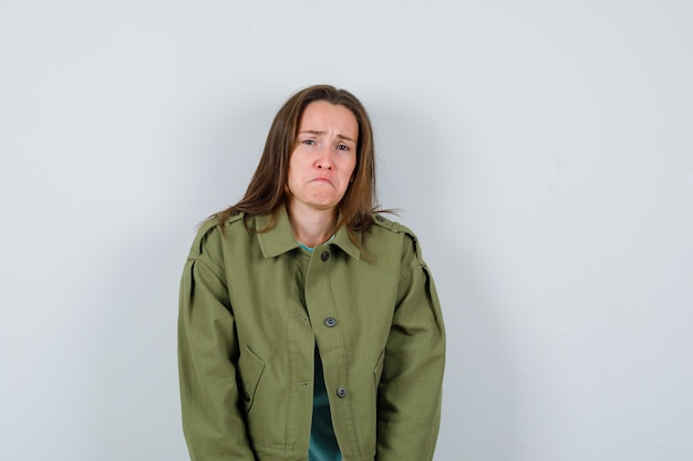 Young lady looking at camera in t-shirt, jacket and looking offended. front view.