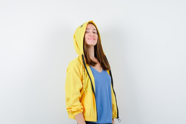 Young lady looking at camera in t-shirt, jacket and looking proud.