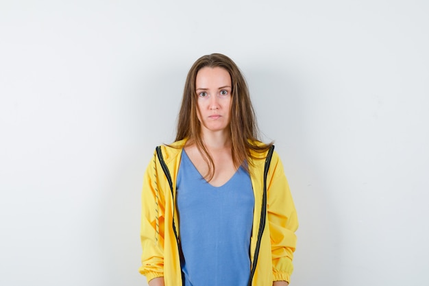 Young lady looking at camera in t-shirt and looking serious. front view.