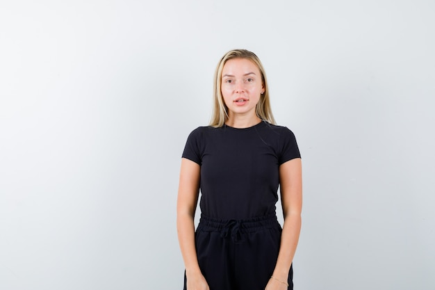 Giovane donna che guarda l'obbiettivo in t-shirt, pantaloni e carino, vista frontale.