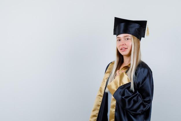 Giovane donna che guarda l'obbiettivo mentre posa in abito accademico e sembra affascinante.