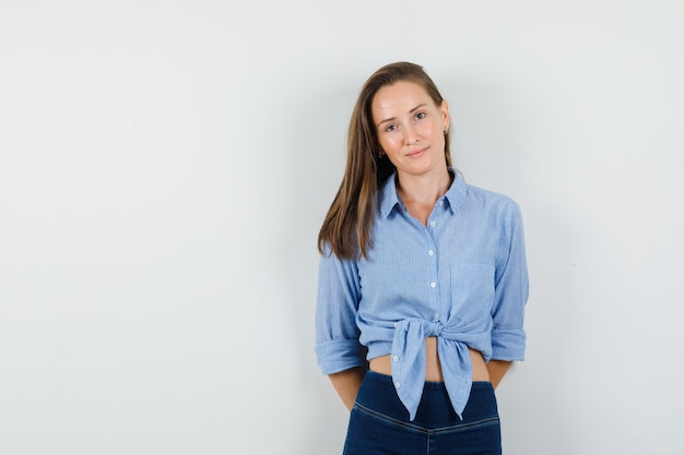 Young lady looking at camera with hands on her back in blue shirt, pants and looking cheery