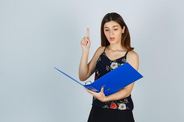Giovane donna che guarda i documenti nella cartella, mostrando il gesto di eureka puntando verso l'alto in camicetta, gonna e guardando stupito, vista frontale.