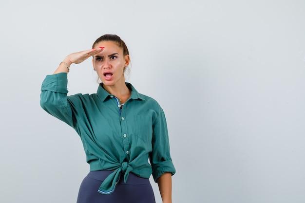 緑のシャツを着て頭上に手を渡して遠くを見て、ショックを受けた若い女性。正面図。
